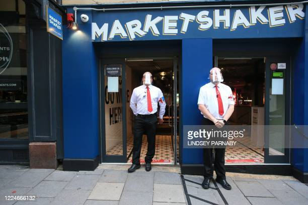 Bouncers wearing visors secure the entrance to a pub in Newcastle, northern England on July 4 as restrictions are further eased during the novel...
