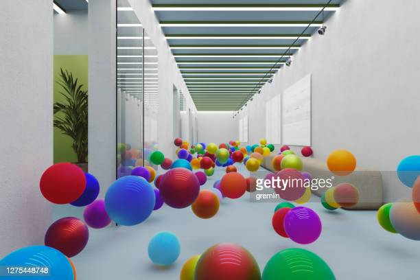 bouncing colorful spheres in empty office - ball stock pictures, royalty-free photos & images