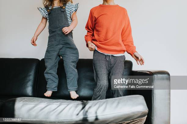 bouncing on a sofa - sofa stock pictures, royalty-free photos & images