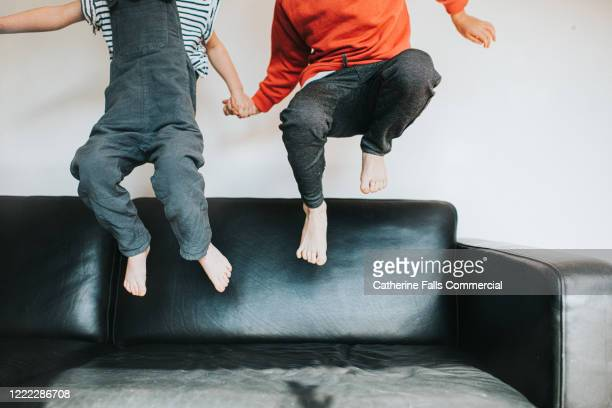 bouncing on a sofa - jumping stock pictures, royalty-free photos & images
