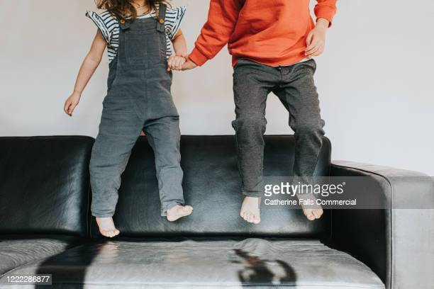 bouncing on a sofa - leather stock pictures, royalty-free photos & images