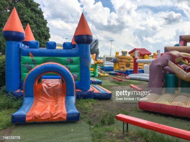 Bouncy Castles Against Cloudy Sky At Park