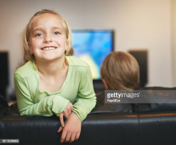 Bouncy little blonde girl  hangs over couch in TV room