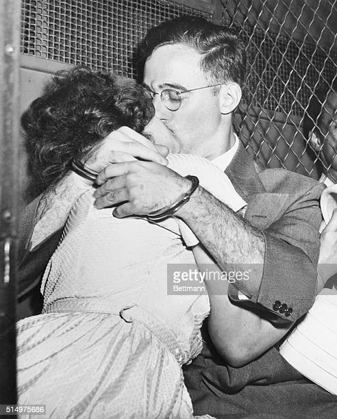 Bound for separate cells, handcuffed Julius Rosenberg and his wife, Ethel, share a fervent kiss in prison van outside Federal Court after arraignment...