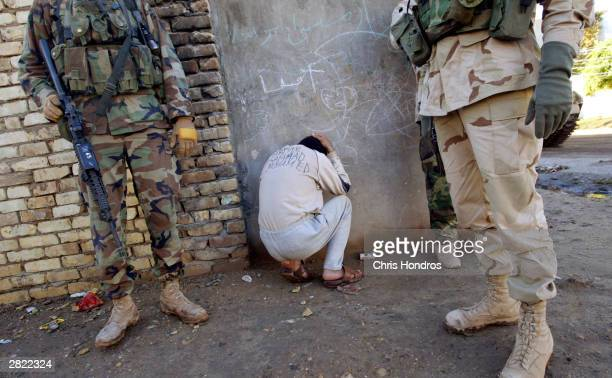 A bound Iraqi informer with his name inked in English across his back crouches beside soldiers in the 4th Infantry Division after providing outdated...