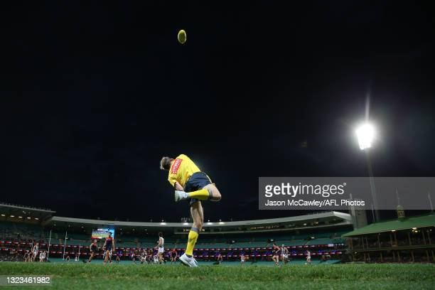 Boundary umpire throws the ball in during the round 13 AFL match between the Melbourne Demons and the Collingwood Magpies at Sydney Cricket Ground on...