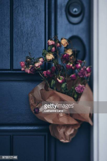 Bouquet of dried roses tied to handle of front door