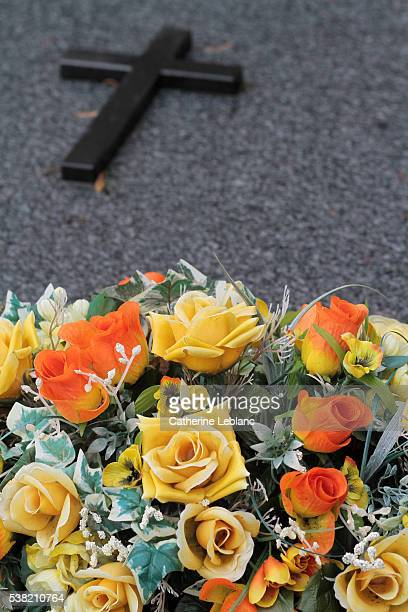 bouquet of flowers and cross on a grave. - crosses with flowers stock pictures, royalty-free photos & images