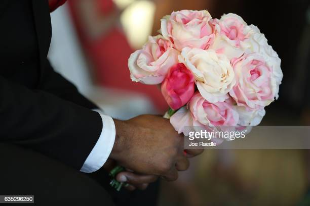 A bouquet of flowers is held by a groom before a group Valentine's day wedding ceremony at the National Croquet Center on February 14 2017 in West...