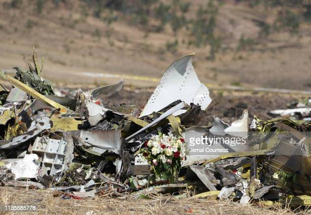 A bouquet of flowers is placed in front of a pile of debris at the scene of the Ethiopian Airlines Flight 302 crash on March 13 2019 in Ejere...