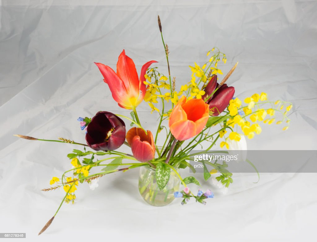 Bouquet Of Freshly Cut Spring Flowers In A Glass Vase Against