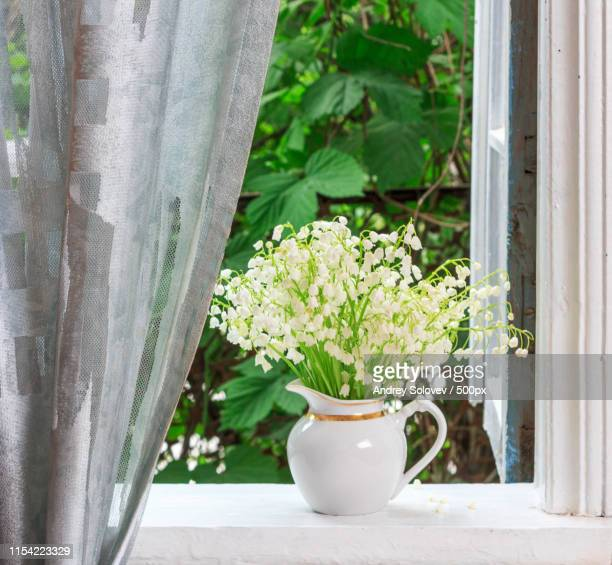 a bouquet of lily-of-the-valley flowers on a windowsill in a country house in the spring morning - bouquet de muguet fotografías e imágenes de stock