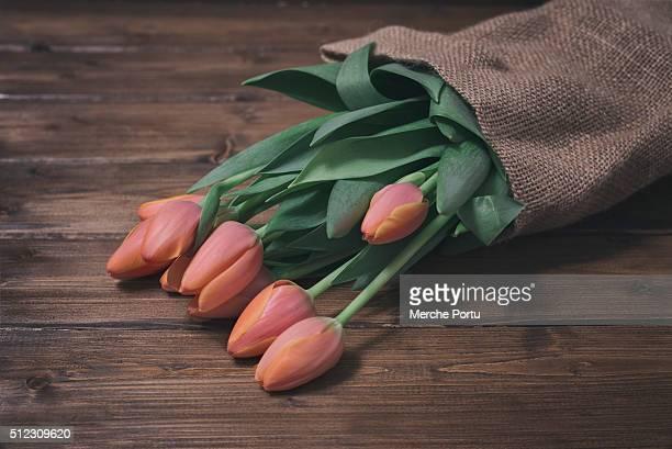 Bouquet of orange tulips on wooden board