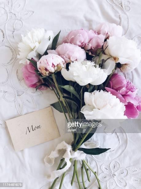 bouquet of peonies next to an envelope with the word mom - muttertag blumen stock-fotos und bilder
