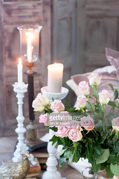 Bouquet of pink roses and burning candles