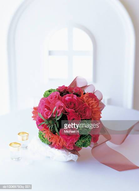 Bouquet of ranunculus, nerine, scabiosa and rose with red ribbon