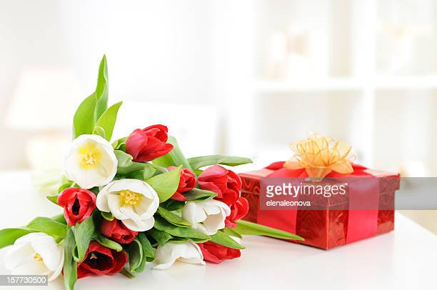 A bouquet of red and white tulips and a red gift box