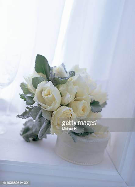 Bouquet of rose and dusty miller on white box