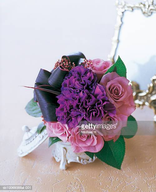 Bouquet of rose, carnation, skimmia, dracaena and lemon leaf in white jewelry box with mirror