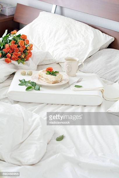 Bouquet of roses and tray with tea and cake on bed