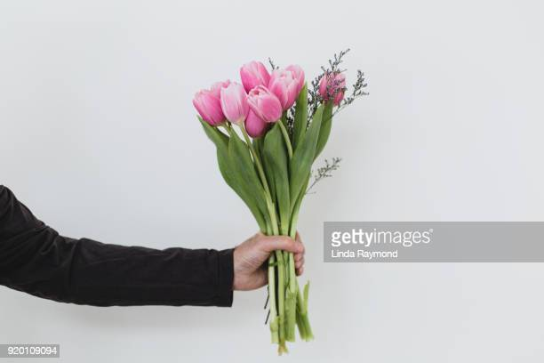 Bouquet of tulips in a hand against a light blue background