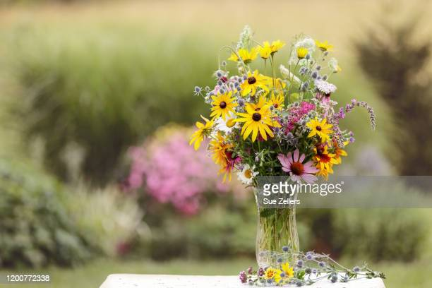 bouquet of wild flowers in vase in a garden - 花瓶 ストックフォトと画像