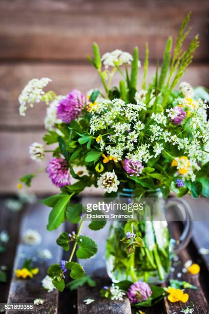 Bouquet of wildflowers in glass jar on wooden table, summer concept