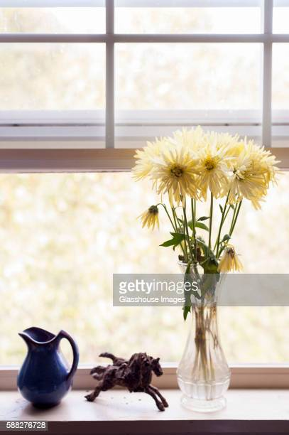 Bouquet Of Yellow Flowers In Vase Next To Horse Sculpture And Blue