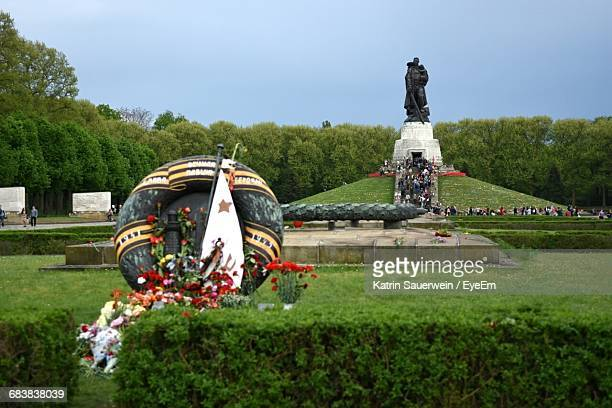 Bouquets By Statues At Soviet War Memorial Against Clear Sky