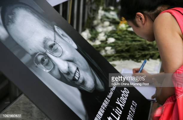 Bouquets of flowers are being placed outside the Chinese government's Liaison Office at the Western District in honor of Liu Xiaobo who died of liver...