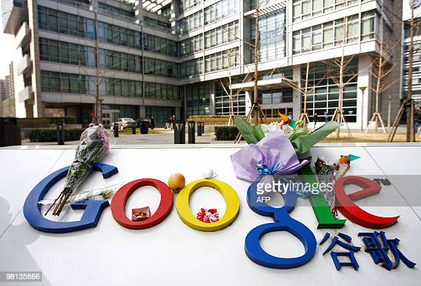 Bouquets of flowers lie on the Google logo outside the company's China head office in Beijing on March 23 2010 after the US web giant said it would...
