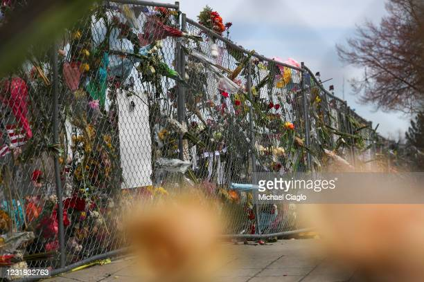 Bouquets of flowers stick through a fence at a makeshift memorial outside a King Soopers grocery store on March 25, 2021 in Boulder, Colorado. Ten...