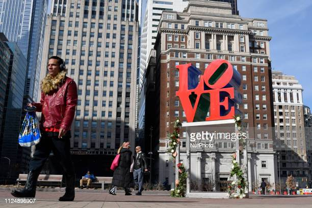 Bouquets of roses decorate the pedestal of the iconic LOVE Park statue in Philadelphia PA on Valentines Day February 14 2019