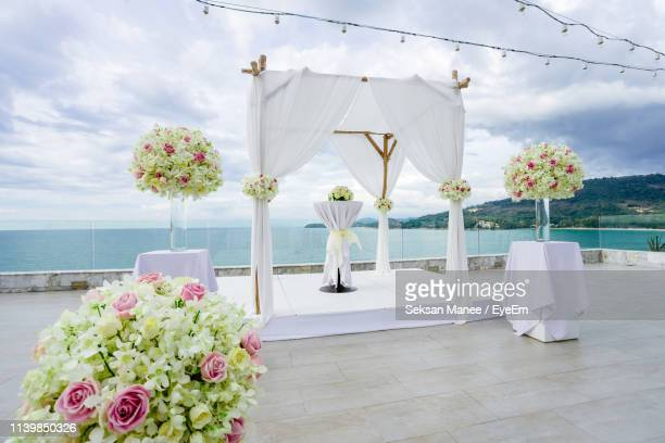 bouquets with entertainment tent arranged by sea against cloudy sky - altar stock pictures, royalty-free photos & images