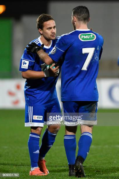 Bourg-en-Bresse's French forward Julien Begue is congratulated by teammates after scoring a goal during the French Cup round of 32 football match...
