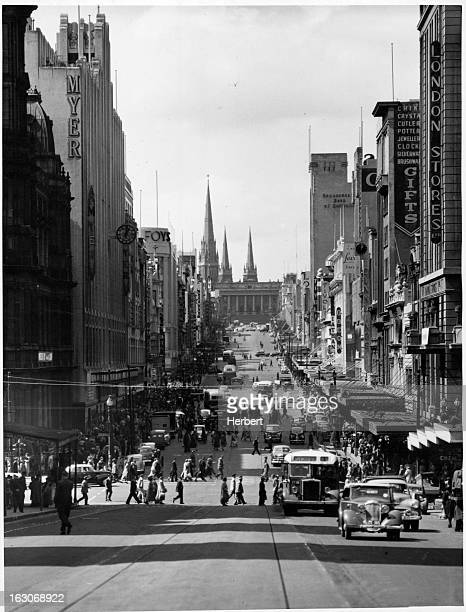 Bourke Street filled with emporiums chain stores all day cinemas and new reels and vaudeville theater at the top of the street is the State...