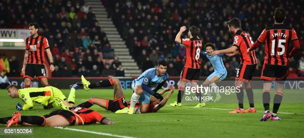 Bournemouth defenders react as Manchester City's Argentinian striker Sergio Aguero celebrates after scoring their second goal during the English...