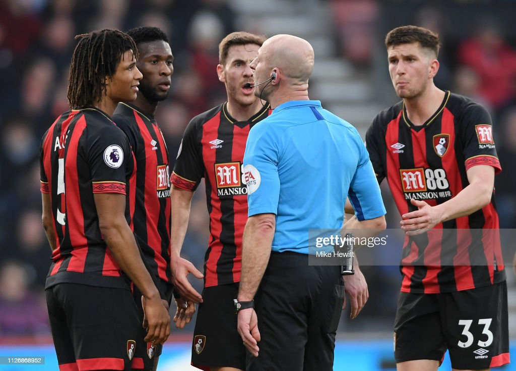 Bournemouth players argue with referee Roger East after he awards a
