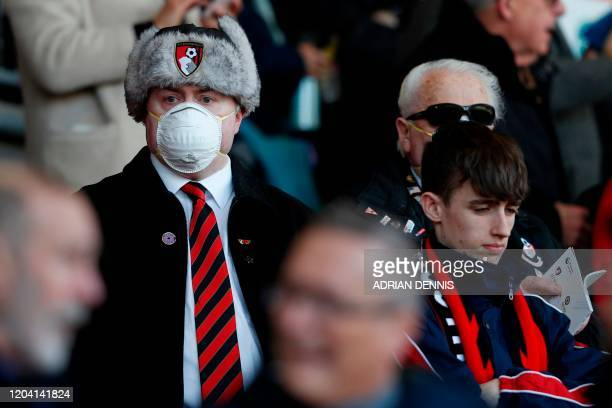 Bournemouth supporter wearing PPE , including a face mask as a precautionary measure against COVID-19, waits in the stands during the English Premier...