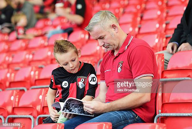 Bournemouth supporters read a matchday programme prior to the Barclays Premier League match between AFC Bournemouth and Tottenham Hotspur at Vitality...
