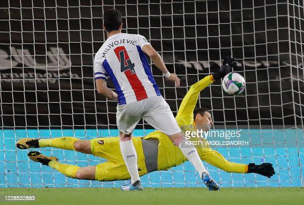 Bournemouth's BosnianHerzegovinian goalkeeper Asmir Begovic dives to save a penalty shot from Crystal Palace's Serbian midfielder Luka Milivojevic...