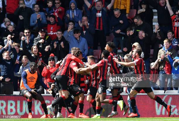 Bournemouth's Dutch defender Nathan Ake is mobbed by teammates after scoring the opening goal in the closing minutes of the English Premier League...