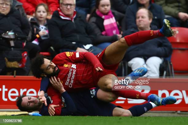 TOPSHOT Bournemouth's English defender Adam Smith and Liverpool's Egyptian midfielder Mohamed Salah collide during the English Premier League...