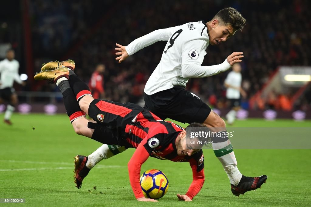 Bournemouth's English defender Adam Smith falls under a challenge from Liverpool's Brazilian midfielder Roberto Firmino during the English Premier League football match between Bournemouth and Liverpool at the Vitality Stadium in Bournemouth, southern England on December 17, 2017. / AFP PHOTO / Glyn KIRK / RESTRICTED TO EDITORIAL USE. No use with unauthorized audio, video, data, fixture lists, club/league logos or 'live' services. Online in-match use limited to 75 images, no video emulation. No use in betting, games or single club/league/player publications. /