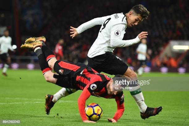 Bournemouth's English defender Adam Smith falls under a challenge from Liverpool's Brazilian midfielder Roberto Firmino during the English Premier...