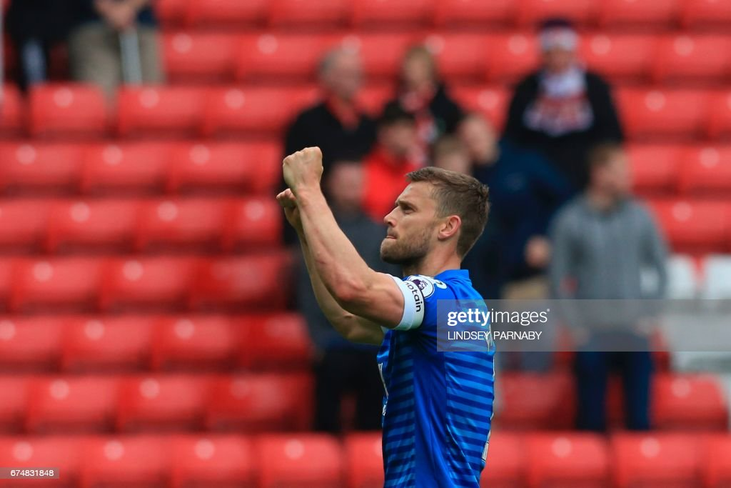 Bournemouth's English defender Simon Francis celebrates with the crowd after winning the English Premier League football match between Sunderland and Bournemouth at the Stadium of Light in Sunderland, north-east England on April 29, 2017. / AFP PHOTO / Lindsey PARNABY / RESTRICTED TO EDITORIAL USE. No use with unauthorized audio, video, data, fixture lists, club/league logos or 'live' services. Online in-match use limited to 75 images, no video emulation. No use in betting, games or single club/league/player publications. /
