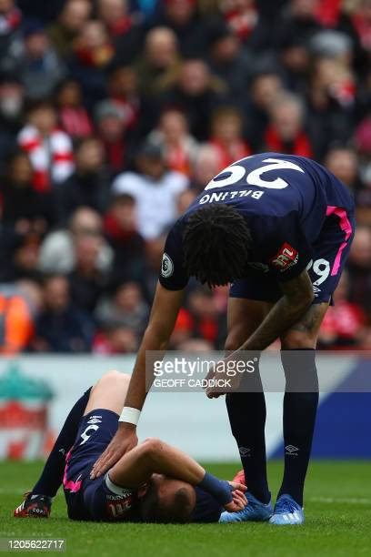 Bournemouth's English defender Steve Cook lies injured AS Bournemouth's Danish midfielder Philip Billing assists during the English Premier League...