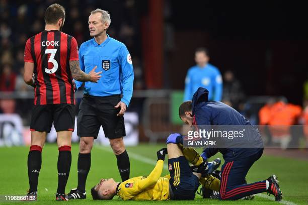 Bournemouth's English defender Steve Cook talks with English referee Martin Atkinson as Arsenal's Brazilian striker Gabriel Martinelli is treated...