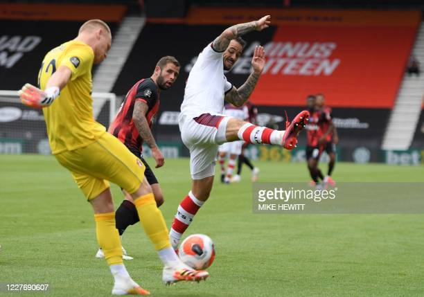 Bournemouth's English goalkeeper Aaron Ramsdale is challenges by Southampton's English striker Danny Ings during the English Premier League football...