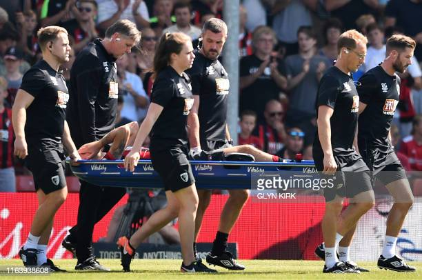 Bournemouth's English midfielder Charlie Daniels is stretchered off injured during the English Premier League football match between Bournemouth and...